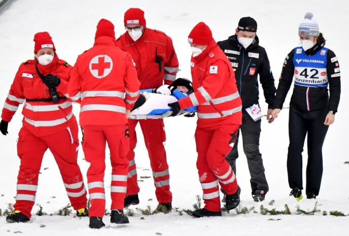 RYSTENDE SCENER: Eirin Maria Kvandal ble fraktet ut av hoppbakken på båre. Foto: NTB