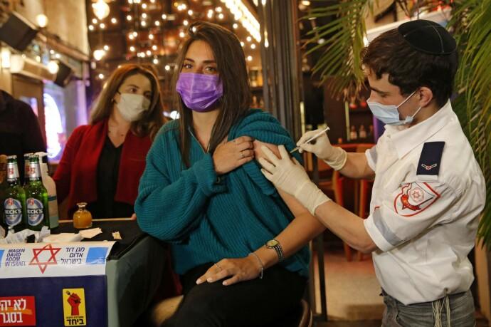 BAR-VAKSINE: En kvinne får satt corona-vaksinen på en bar i kystbyen Tel Aviv torsdag denne uka. Foto: AFP / NTB