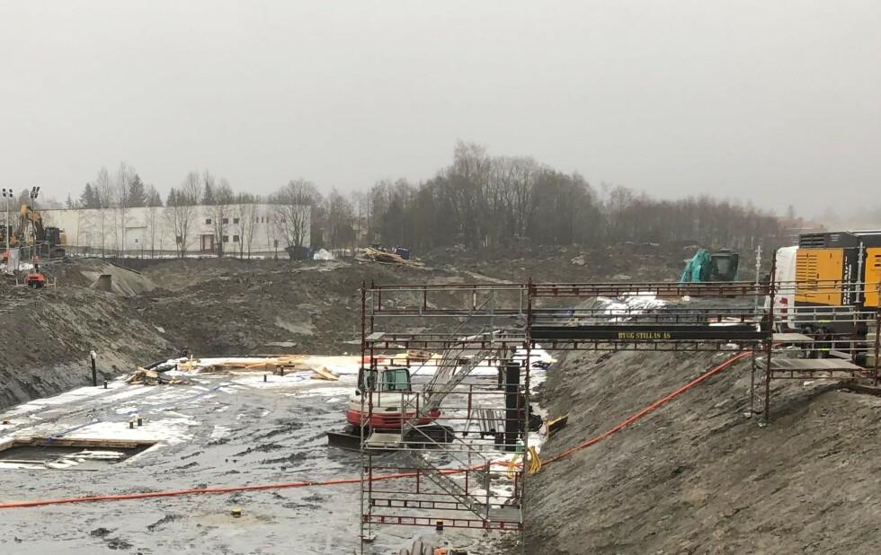 19. desember 2020: Utgravd kjeller for boligblokk for Vestvang 2. I bakgrunnen ses mellomlagrede masser på skråningstoppen av ravinen mot nedenforliggende boligfelter. Foto: Privat.