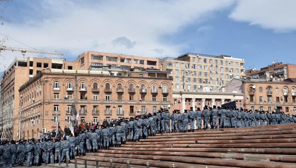 BLOKKADE: Armensk politi blokkeren en gate foran et av regjeringsbyggene under en demonstrasjon initiert av opposisjonen i Armenias hovedstad Jerevan, tirsdag. Foto: Karen Minasyan / AFP / NTB