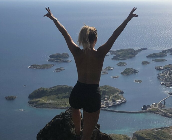 POSERER TOPPLØS: Carina Dahl legger ikke skjul på at hun selv er en del av den nye trenden. Her poserer hun etter en topptur i Henningsvær i 2019. Foto: Privat