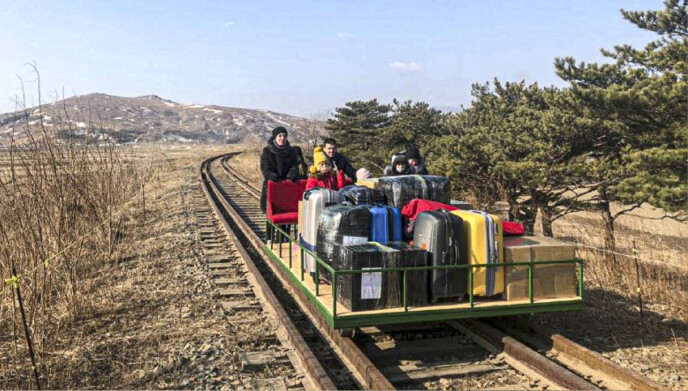 SKYVES OVER GRENSA: Reiseselskapets eneste mann fungerte som motor på toget, mens barn og bagasje var trygt plassert på dresinen. Foto: Russlands utenriksdepartement/NTB.