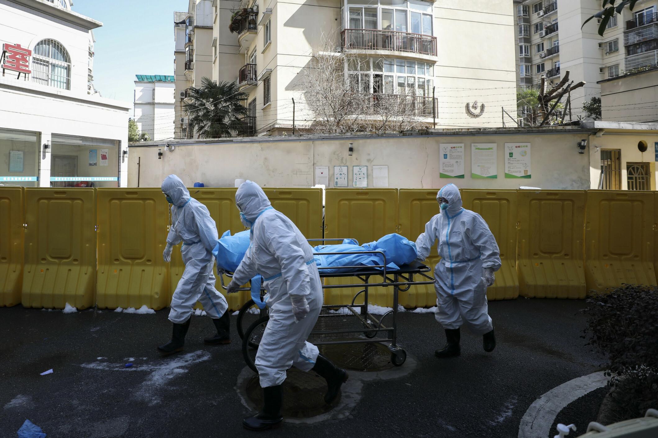 DØDE: 16. februar 2020: Medisinsk personell frakter ut en person som døde av COVID-19 på et sykehus i Wuhan. Foto AP/NTB