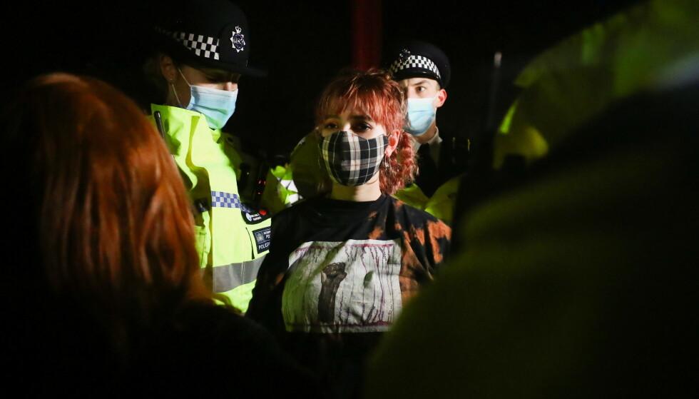 KONFRONTASJON: Politiet i London pågrep flere personer som deltok i en minnemarkering for drapsofferet Sarah Everard lørdag kveld. Nå får de hard kritikk fra mange hold. Foto: REUTERS/Hannah McKay