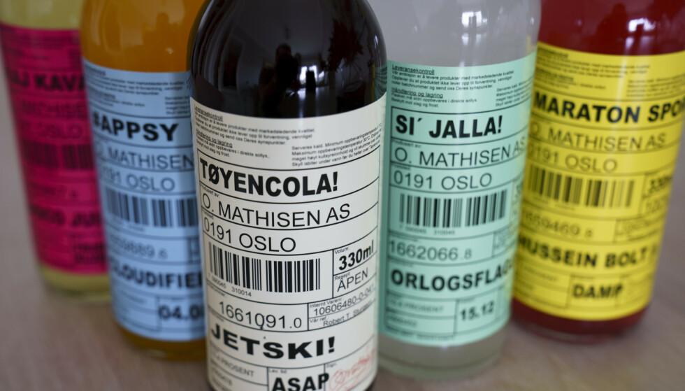 TØYENCOLA: Flere har reagert på etiketten til O. Mathisen sine varianter av Tøyencola. Bak på etiketten på smakene Kaj Kavaj, #Appsy, Maraton sport og SI ` Jalla! står det «WWW.DINERETTIGHETERHER.COVID.1984.5G.ID2020.EVENT201». Flasken hvor det står «Tøyencola» er den eneste som ikke har den teksten. Foto: Torstein Bøe / NTB