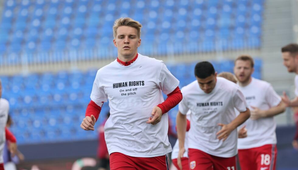 QATAR-MARKERING: Landslaget gjorde som varslet. På oppvarmingen brukte samtlige av spillerne den samme t-skjorten, som under Gibraltar-kampen. Foto: Geir Olsen / NTB