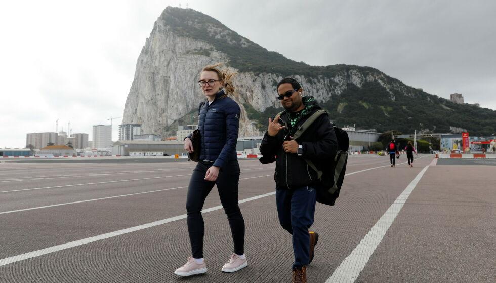HARDT RAMMET: Innbyggere fra Gibraltar krysser rullebanen på flyplassen på vei inn i Spania uten munnbind. Et påbud om munnbind utendørs er opphevet i Gibraltar, som er svært hardt rammet av epidemien, fordi tilstrekkelig mange er vaksinert. Etter en avtale skal grensa til Spania være åpen, mens EU og Spania rykker inn med grensevakter på flyplassen og i havna i dette britiske området. Foto: REUTERS / NTB / Jon Nazca