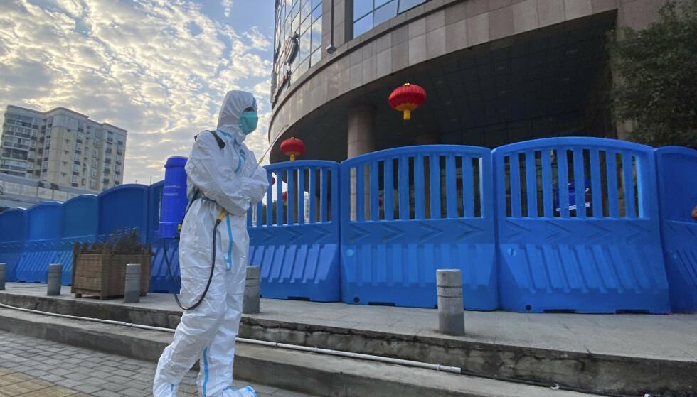 En arbeider i beskyttelsesdrakt som bærer desinfiseringsutstyr går utenfor Wuhan Central Hospita, 6 februar, 2021. Foto: Photo/Ng Han Guan/ NTB