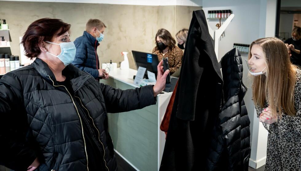 PASSKONTROLLØR: En frisør i Køge sjekker at en kunde har corona-opplysningene før hun blir sluppet inn i salongen. Foto: Mads Claus Rasmussen, Ritzau/Reuters/NTB.