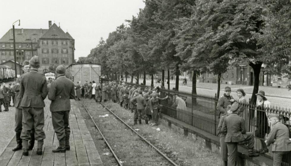 FRONTKJEMPERE: Bildet er fra jernbanestasjonen i München 23. juli 1942, og viser et studentkompani med tyske medisinstudenter som tar farvel med venner og familie, mens de gjør seg klare for avreise til østfronten. Foto: NTB / AKG / George Wittenstein
