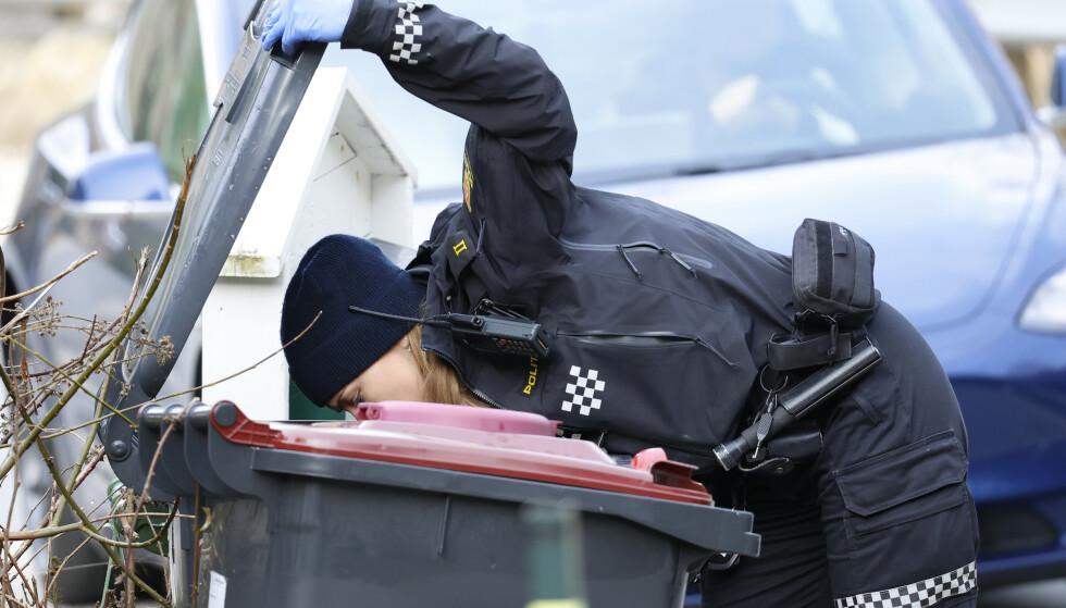 UNDERSØKER SØPLA: Politiets etterforskere på stedet saumfarer området - blant annet undersøker de søppelkassene utenfor boligen. Foto: Tor Erik Schrøder / NTB