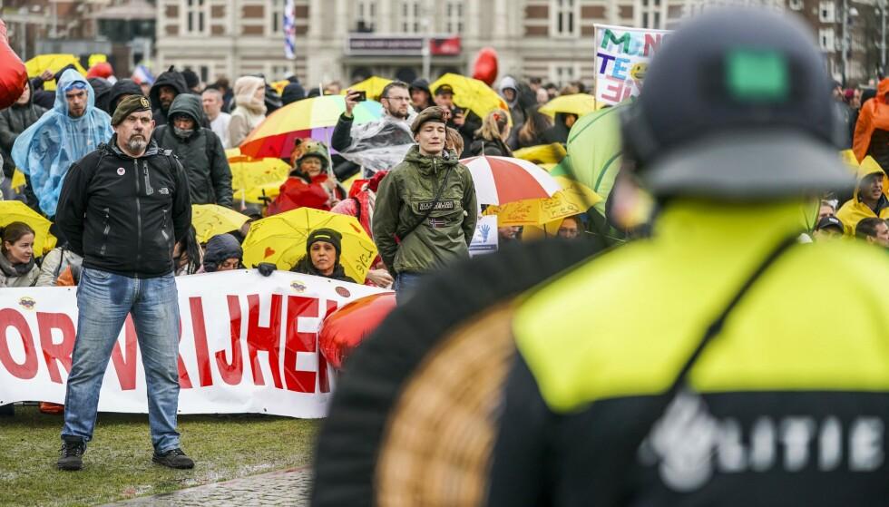 STOR MISNØYE: I Amsterdam måtte politiet ta i bruk vannkanoner mot demonstrantene som hadde tatt til gatene for å vise sin misnøye med regjeringens håndtering av pandemien 28. mars. Foto: Jeroen Jumelet / ANP / AFP / NTB