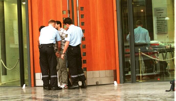 DRAP: Redningsmannskaper behandlet stefaren innenfor glassveggen på tinghuset i Oslo, mens politiet ransaket gjeringsmannen. Foto: Bjørn Sigudsøn / NTB