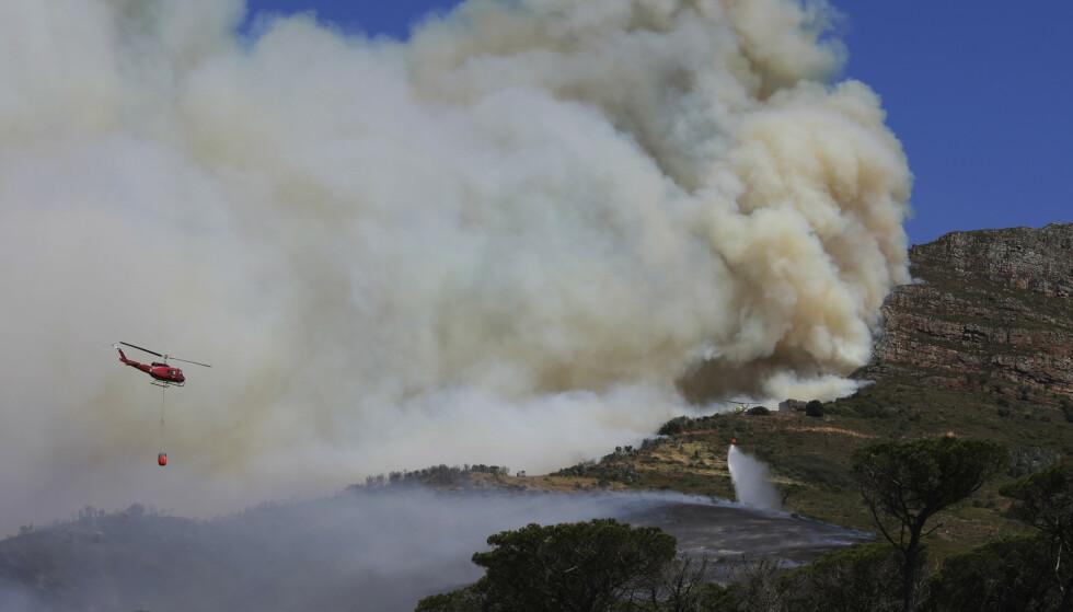 SLUKKING: Helikoptere flyr inn vann over skogmrådet som brenner. Foto: Nardus Engelbrecht / AP / NTB