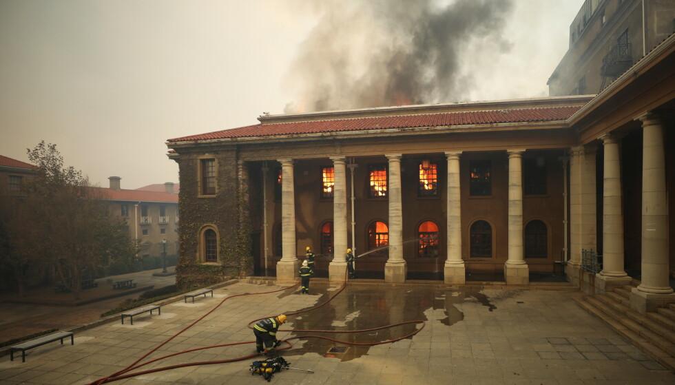 UNIVERSITETET: Branmennene kjemper mot flammene på det historiske biblioteket på univeristetet i Cape Town. Alle studentene er evakuert. Foto: Mike Hutchings/Reuters/NTB.