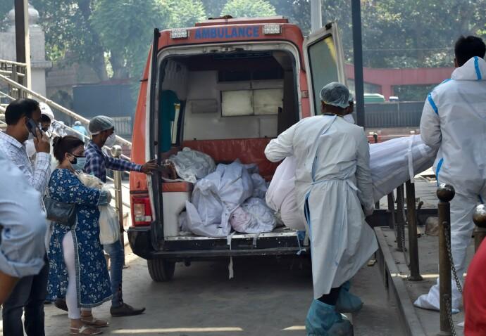 MANGE DØDE: Det dør nå så mange av covid-19 at flere indiske krematorium brenner de døde hele døgnet. Flere store byer melder om mye større kremeringer og begravelser enn landets offisielle tall. Her bæres nok et covid-offer inn i en ambulanse i New Delhi. Foto: Hindustan Times / NTB