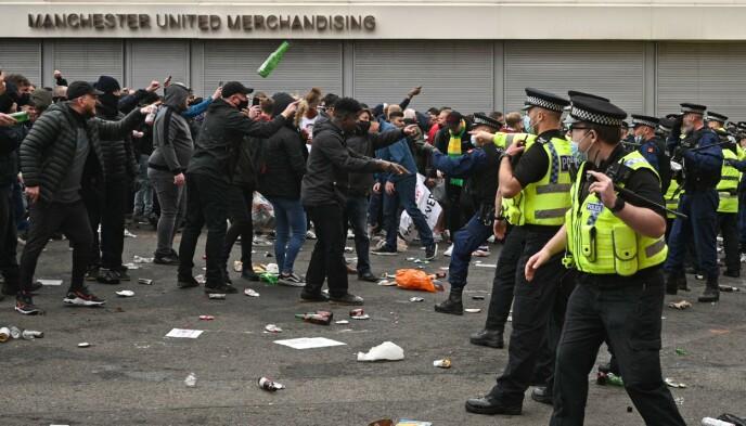 FLASKER: Flere glassflasker ble kastet mot politiet utenfor Old Trafford søndag. Foto: Oli SCARFF / AFP)