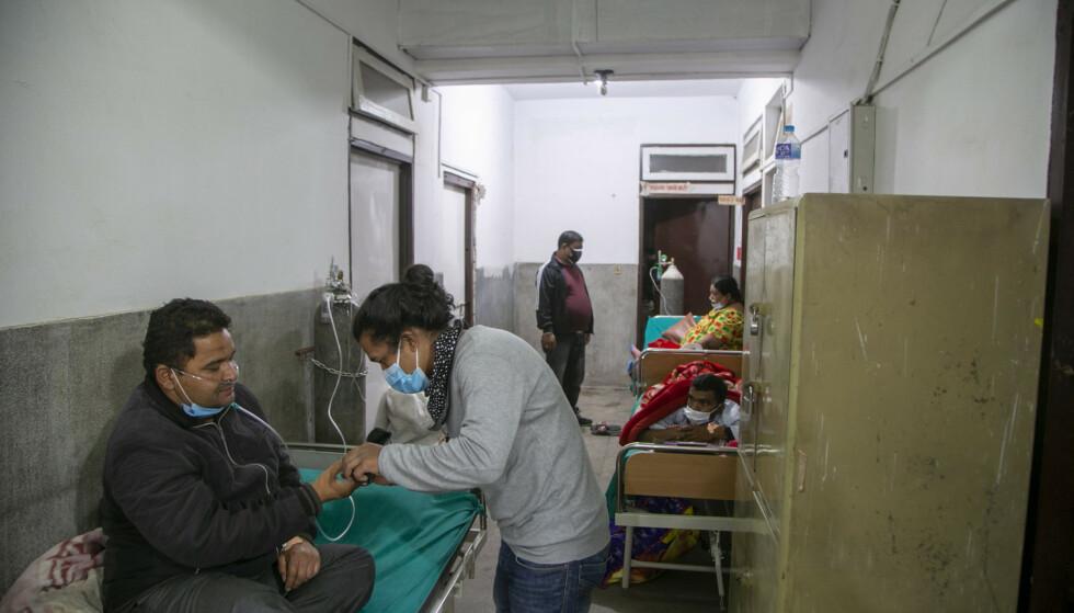 LEGEVAKTA: Et familiemedlem gir medisin til en coronasyk mann i gangen på legevakta i et sykehus i Katmandu. Bildet er tatt 5. mai 2021. Foto: AP Photo/Niranjan Shrestha / NTB