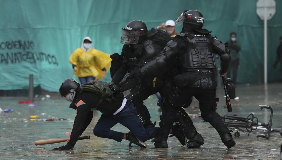 POLITIET FÅR KRITIKK: Politiet pågriper en demonstrant i Bogotá onsdag. Foto: Fernando Vergara / AP / NTB