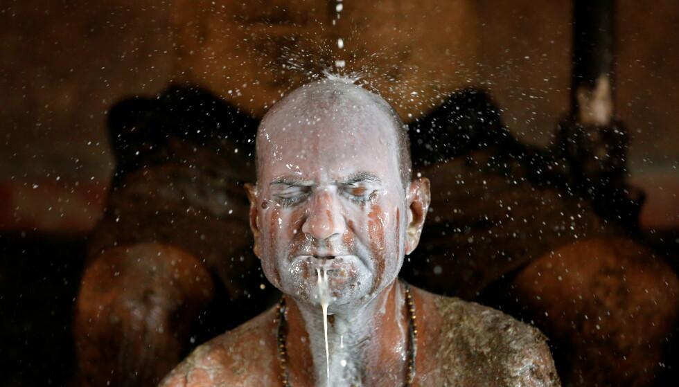 SKYLLER: En mann får vasket vekk kumøkka med melk. Foto: Amit Dave / Reuters / NTB