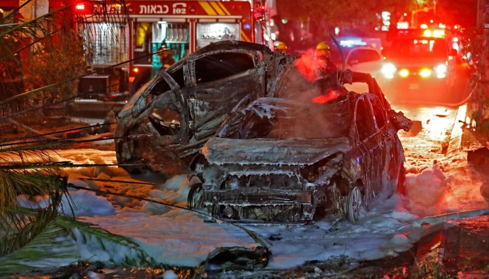 MANGE ANGREP: Flere biler sto i brann etter rakettangrep mot Holon sør for Tel Aviv tirsdag kveld. Også en buss skal ha blitt truffet. Foto: Ahmad Gharabli / AFP / NTB