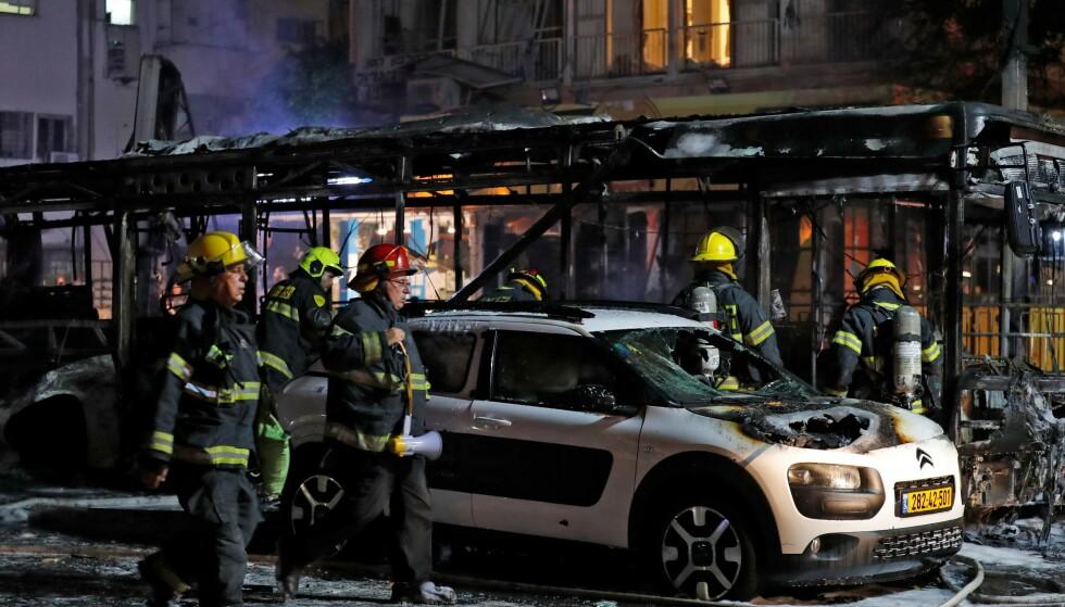 TRAFF BUSS: En buss i Holon sør for Tel Aviv skal ha blitt truffet av raketter tirsdag kveld. Ifølge israelske medier skal to voksne og et barn ha blitt såret i angrepet. Foto: Ahmad Gharabli / AFP / NTB