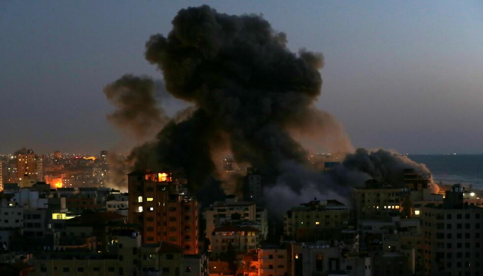 ANGREP BOLIGBLOKK: Røyk stiger fra et område på Gaza rammet av israelske luftangrep tirsdag kveld. En boligblokk på 13 etasjer raste som følge av angrepet. Foto: Ibraheem Abu Mustafa / Reuters / NTB