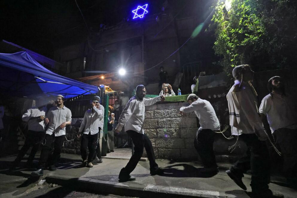 UTE ETTER BRÅK: Israelske bosettere danser foran ett av husene i det palestinske nabolaget Sheikh Jarrah i Øst-Jerusalem, som de har annektert. Dette er ulovlig etter internasjonal rett. Bosetternes ønske om å kaste ut de palestinske familiene som bor her, var gnisten som igjen fyrte opp konflikten mellom israelere og palestinere. Foto: AFP / NTB