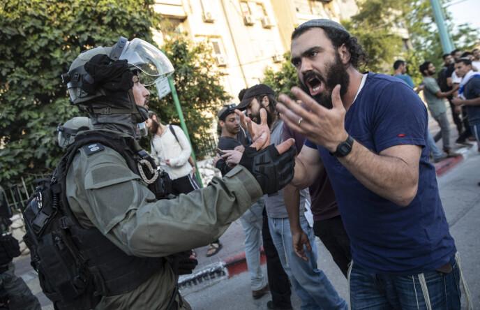 STOPPER SINE EGNE: Israelsk opprørspoliti forsøker å stoppe en jødisk høyreekstrem fra å fortsette å slåssinga mellom israelske arabere og jøder i den israelske byen Lod, som ligger like ved hovedflyplassen Ben Gurion. Her bor både jøder og arabere, side om side. Stort sett fredelig, men de siste dagene har det vært en rekke kamper mellom naboer. Foto: AP / NTB