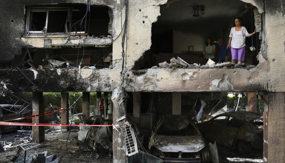 PÅ BAR BAKKE: Den israelske Sror-familien står og ser ut av sin utbombede leilighet i Petah Tikva, like før Tel Aviv. Leiligheten ble truffet av en rakett fra Gaza, natt til torsdag. Foto: Ap / NTB