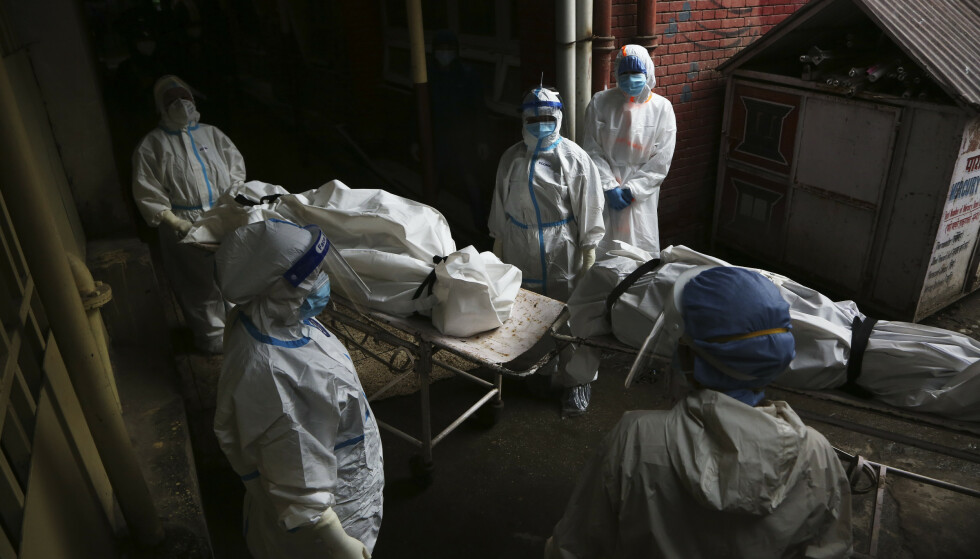NEPAL: Helsearbeidere jobber med å frakte personer som døde med coronasmitte til kremasjon. Bildet er tatt i Katmandu, Nepal, 12. mai 2021. Foto: AP Photo/Niranjan Shrestha / NTB