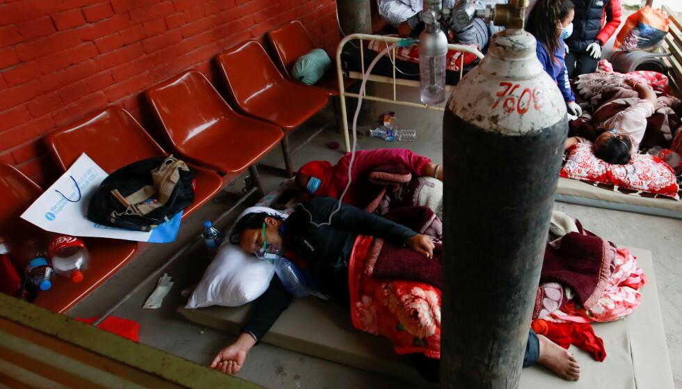 I GANGEN: Pasienter får oksygen mens de sover på gulvet i gangen i et sykehus, på grunn av mangel på senger. Bildet er tatt 10. mai 2021 i Katmandu. Foto: REUTERS/Navesh Chitrakar / NTB