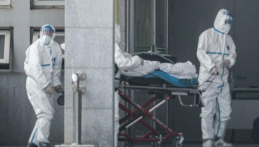 BEGYNNELSEN: Helsepersonell avbildet mens de frakter en pasient inn til et sykehus i den kinesiske storbyen Wuhan den 18. mars 2020. Foto: STR / AFP / NTB