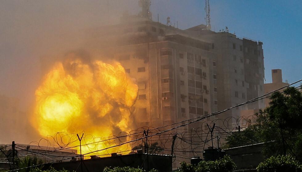 KOLLAPSET: En vegg av flammer står ut av Jala Tower på Gazastripen kort tid etter det israelske luftangrepet lørdag ettermiddag. Foto: Mohammed Abed / AFP / NTB