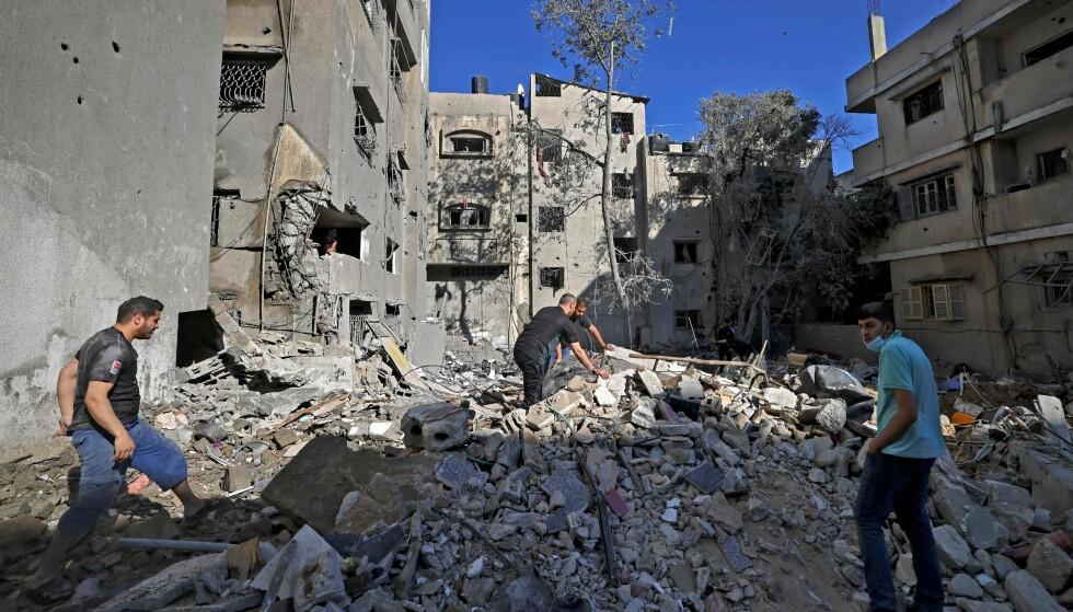 ENORME ØDELEGGELSER: Palestinere leter etter eiendeler i ruinene etter et israelsk luftangrep mot Gaza lørdag. Foto: Mahmud Hams / AFP / NTB
