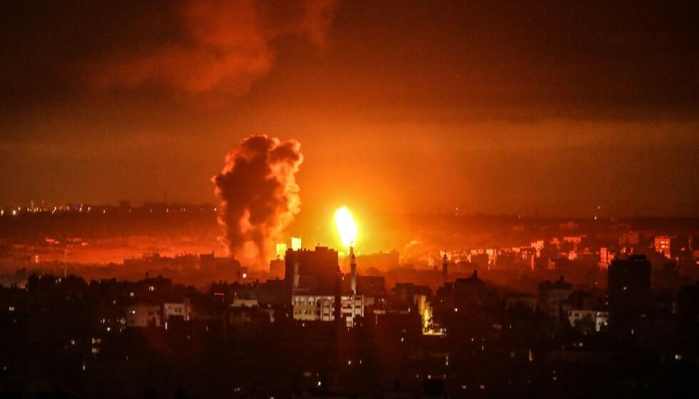 FLAMMER: Flammer kan ses i Gaza by i det fjerne, mens kamper fortsetter for syvende dag. Foto: APA Images / Shutterstock / NTB