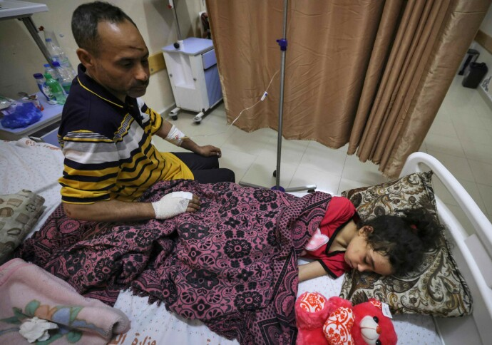 SLITNE: Pappa Riad Ishkontana passer på dattera Suzy mens hun tar en hvil på Shifa-sykehuset, der de bor side om side. Foto: AFP / NTB