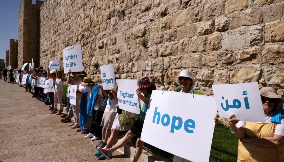 VIL HA FRED: De er ikke i flertall, og blir sjelden hørt nok, men ved en av murene i Jerusalems gamleby møttes både israelere, palestinere og internasjonale aktivister og ba om fred og sameksistens onsdag denne uka. Foto: Reuters / NTB