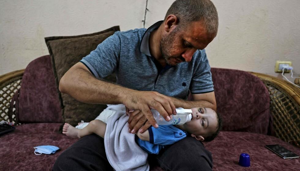 MISTET MANGE: Palestinske Mohammad al-Hadidi er i brorens leilighet i Gaza, der han gir sønnen sin melk fra flaske. Den lille gutten Omar ble dratt levende ut av ruinene etter at huset deres ble bombet. Hans mor og fire søsken er ennå ikke funnet. Foto: AFP / NTB