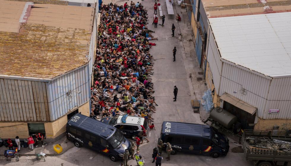 MINDREÅRIGE: Mindreårige som krysset grensa uten foresatte ble samlet på utsiden av et varehus, som ifølge nyhetsbyrået AP ble brukt som et midlertidig oppholdssted mens de ventet på å bli testet for covid-19. Foto: AP Photo/Bernat Armangue / NTB