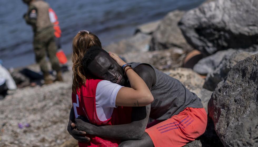 OMFAVNES: En migrant trøstes av et medlem av det spanske Røde Kors, ved Ceuta. Foto: AP Photo/Bernat Armangue