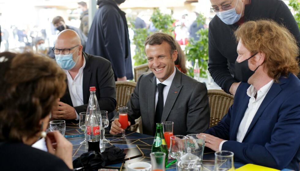 VALGKAMP: President Emmanuel Macron tok et glass ved et bord utendørs i Nevers, idet Frankrike åpnet litt opp, åpenbart som et ledd i den politiske kampen foran neste års valg. Foto: Thibault Camus / AFP NTB