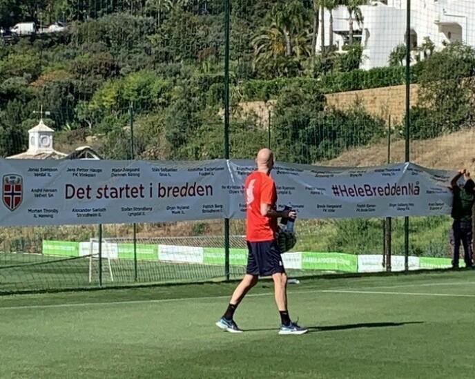 BREDDESTØTTE: Ståle Solbakken kaster et blikk på bannerne til støtte for breddefotballen før dagens trening. Foto: Tore Ulrik Bratland