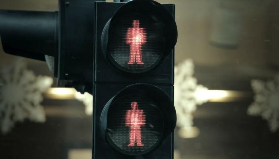 TRAFIKKLYS: Helt i begynnelsen av filmen krysser Mona Juul gaten i Oslo sentrum og vi ser et trafikklys med to røde menn. Foto: HBO