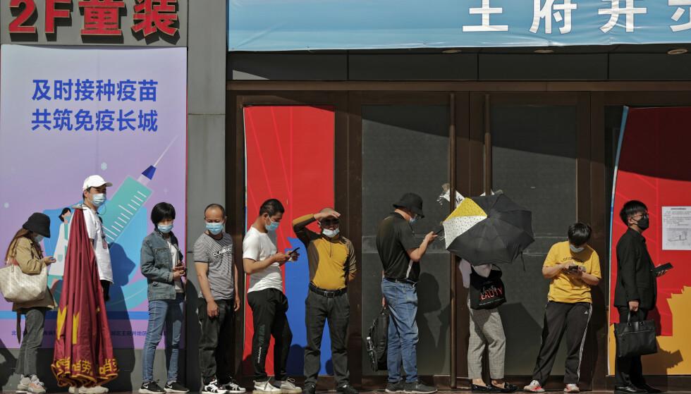 VAKSINEKØ: Kinesere i kø for å få koronavaksine i Beijing 17. mai. På en plakat ved vaksinasjonssenteret står følgende slagord: «Vaksinasjon til rett tid for sammen å bygge en kinesisk mur av immunitet». Foto: Andy Wong / AP / NTB