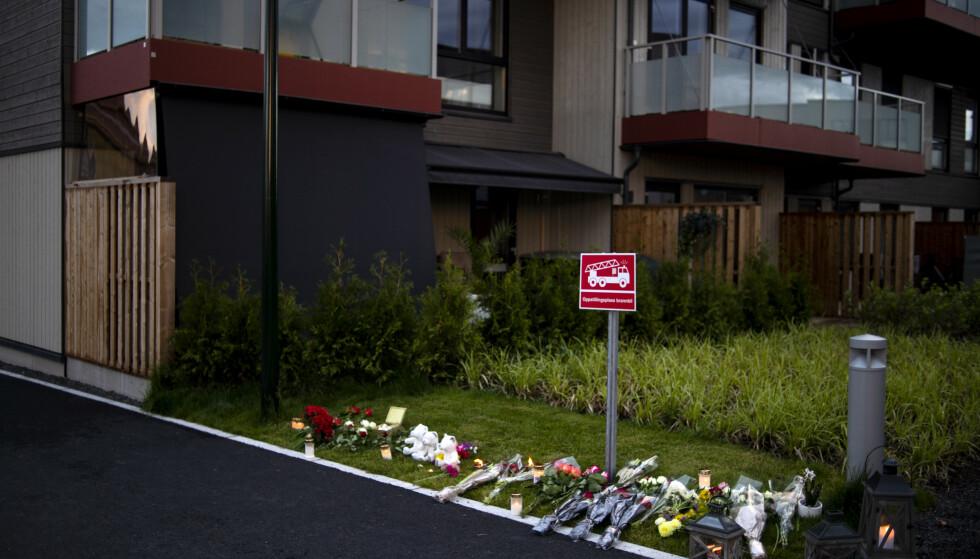 LYS OG BLOMSTER: Folk la ned lys og blomster utenfor boligblokka på Finstadjordet etter at drapene ble kjent. Foto: Annika Byrde / NTB