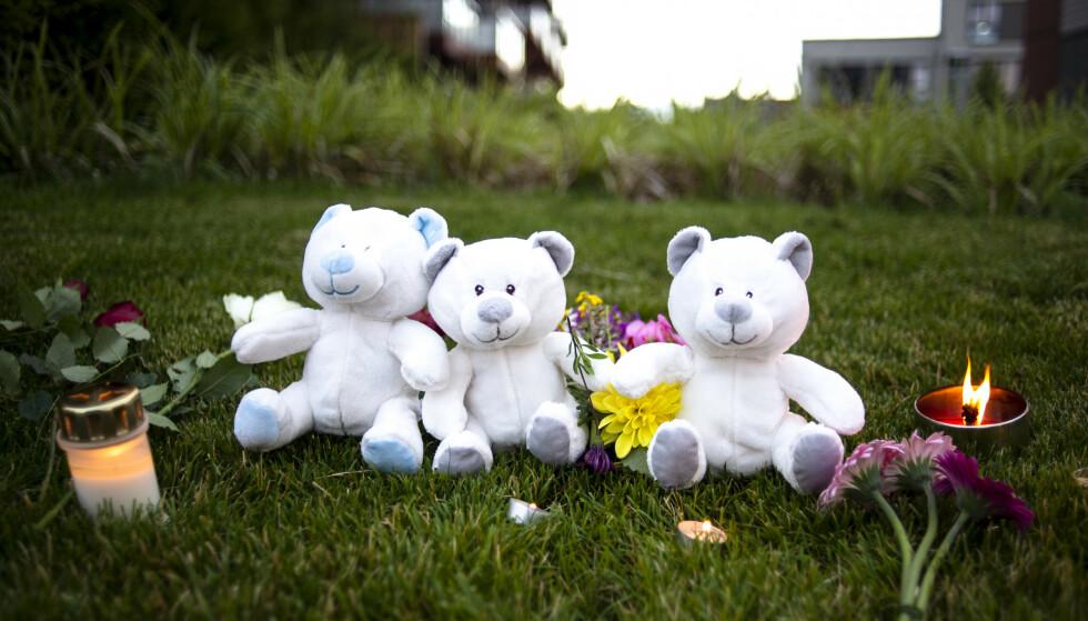 LYS, BLOMSTER OG BAMSER: Folk la ned lys, blomster og bamser utenfor den tiltalte morens hjem etter at sønnene hennes ble funnet drept i leiligheten 19. juli i fjor. Foto: Annika Byrde / NTB