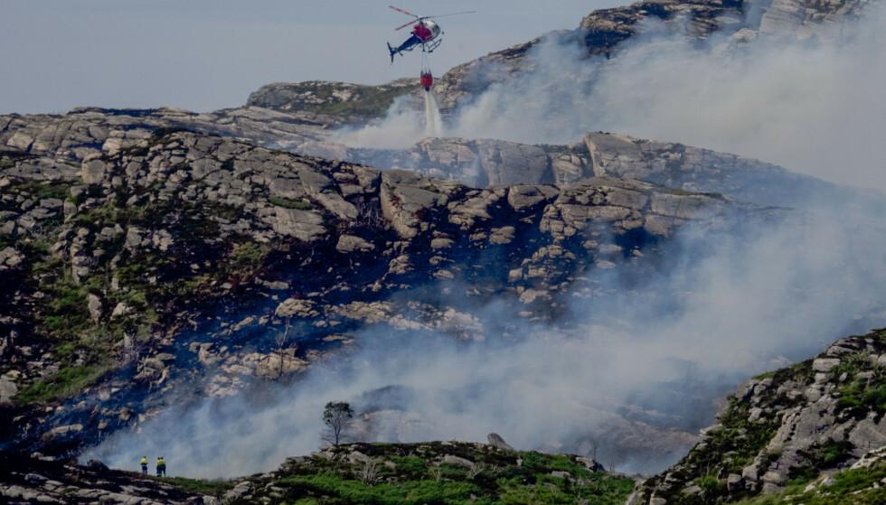 BRANN: Både mannskap på bakken og helikopter er i aksjon for å slokke gressbrannen på Sotra som blusset opp igjen onsdag. Foto: Paul S. Amundsen / NTB
