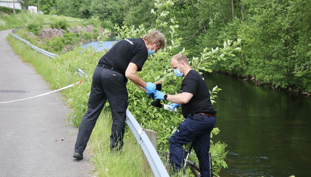 ETTERFORSKER: Politiets kriminalteknikere jobber ved elvebredden, hvor de blant annet undersøker jentas sykkel. Foto: Theo Aasland Valen
