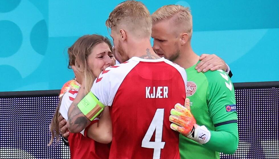 SJOKK: Eriksens kone Sabrina Kvist Jensen ble trøstet av lagkaptein Simon Kjær og keeper Kasper Schmeichel. Foto: WOLFGANG RATTAY / various sources / AFP)